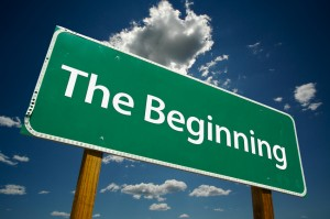 """The Beginning"" Road Sign with dramatic blue sky and clouds."